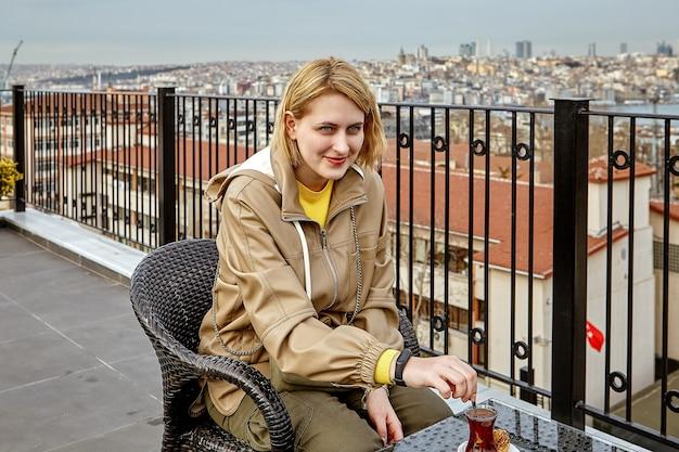 イスタンブールの街並みを見下ろすホテルの屋上でお茶を飲み、ガラスの砂糖をかき混ぜる若いヨーロッパの女性。