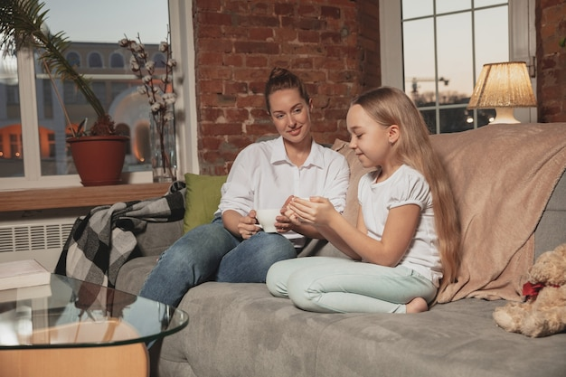 お茶を飲む、話す。隔離された、家族の時間の居心地の良い、快適さ、家庭生活の間に自宅で自己断熱中の母と娘。陽気で幸せな笑顔のモデル。安全、予防、愛の概念。