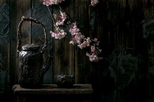 Чайное чаепитие ваби саби в японском стиле из керамической чашки из темной глины и чайника с цветущими ветвями вишни. темная деревянная стена. копировать пространство