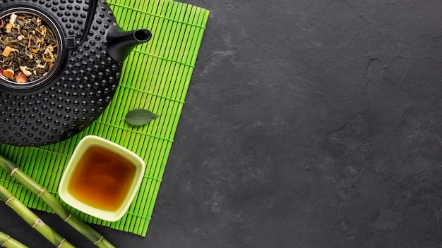 Tea and dry herbs on green placemat over black surface