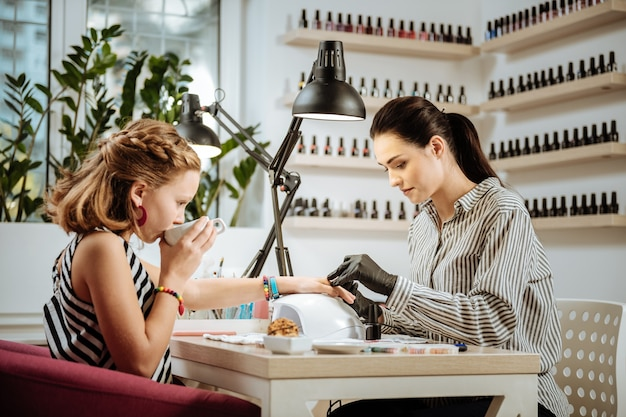 Tea during manicure. stylish teenage girl wearing accessories and striped dress drinking tea during manicure