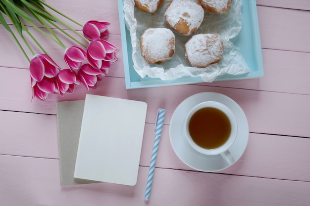 Tea.flat lay.spring to-do list.pink tulips flowers, blank notebook, cup of tea and blue tray with donuts.