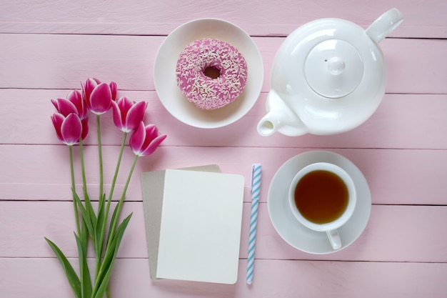 Tea.flat lay.spring to-do list.pink tulips flowers, white teapot, blank notebook, cup of tea and pink donut on a pink  background.