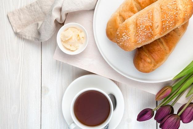 Чай, свежий хлеб и цветы на светлом фоне. вид сверху с копией пространства.