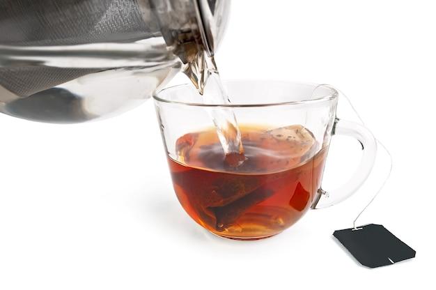 ガラスのボウルの袋からお茶、白い背景で隔離のお湯の急須