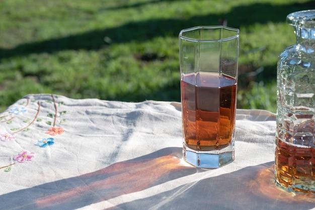 ティーグラスは日没時に庭のリネンテーブルにクローズアップ