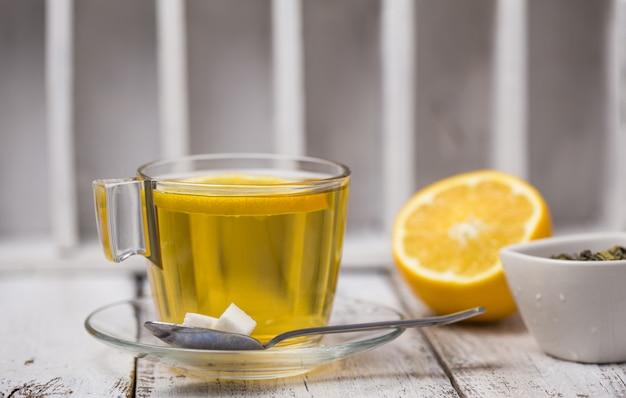 Tea in a glass cup mint leaves dried tea sliced lemon.