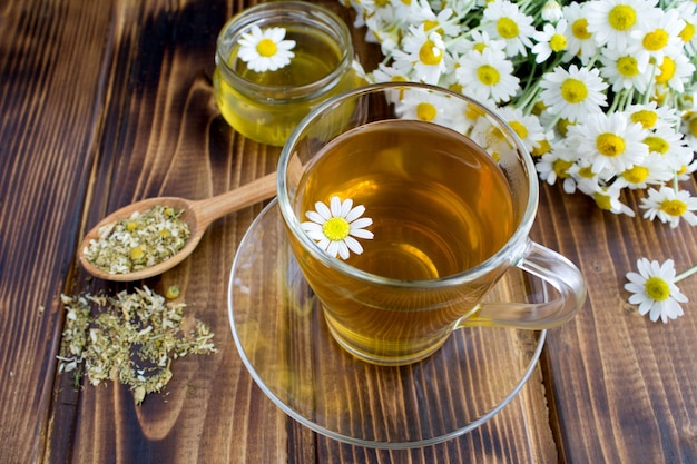Tea in the glass cup with chamomile and honey on the brown wooden table