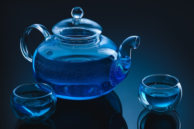 Tea in a glass teapot and cups