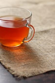 Tea in a glass transparent mug on burlap tablecloth.