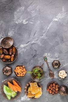 Стакан чая с фруктами даты и соты на сером столе