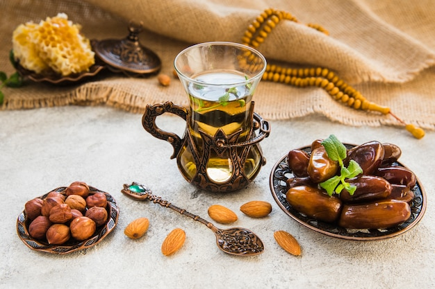 Tea glass with dates fruit and different nuts