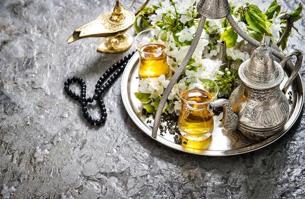 Чайные стаканы и чайник, арабский фонарь и четки. украшение исламских праздников. рамадан карим. концепция восточного гостеприимства