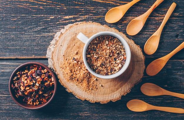 Erbe del tè in una ciotola e tazza con la vista superiore dei cucchiai su un troncone di legno e su un fondo di legno scuro