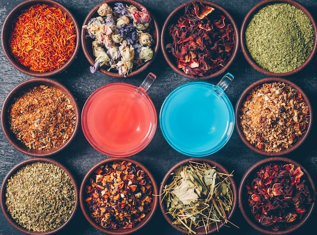 Tea herbs in a bowls with red and blue colored water top view on a dark textured background