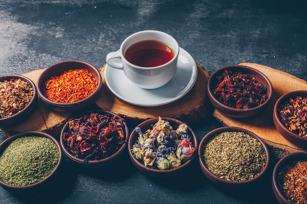 Tea herbs in a bowls with wood stubs and a cup of tea high angle view on a dark textured background. space for text