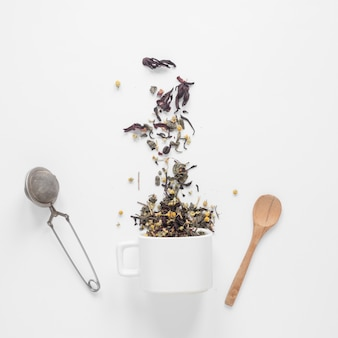 Tea herbs falling from cup with strainer and spoon on white backdrop