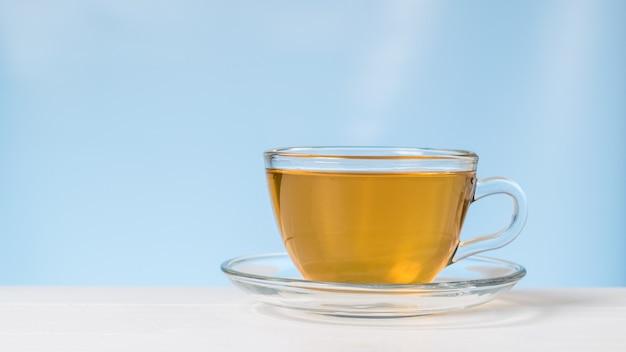 青い背景の上の白いテーブルの上のガラスのカップとソーサーのお茶。健康に役立つ爽快なドリンク。