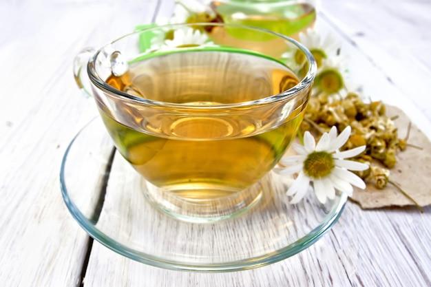 유리 컵에 담긴 차, 종이에 마른 카모마일 꽃, 밝은 나무 판자 배경에 신선한 데이지 꽃