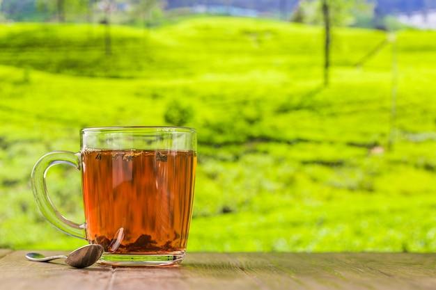 Чай в стеклянной чашке на деревянном столе и поверхности чайных плантаций