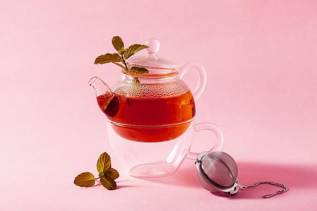 ピンクの背景のガラスのティーポットと金属注入フィルターでお茶