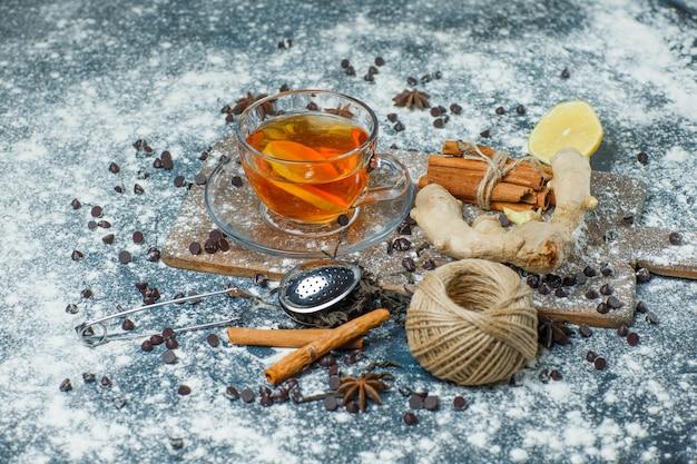 マグカップに入ったお茶、小麦粉、チョコチップ、ストレーナー、スパイス、レモンのハイアングル、コンクリートとまな板