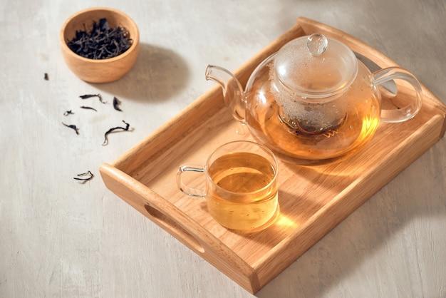 透明なカップのお茶と木製の背景のティーポット
