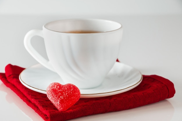 Чай в белой чашке и мармелад в форме сердца на белой поверхности.