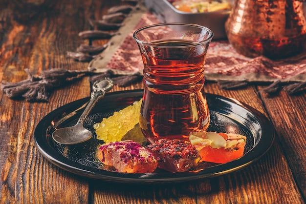 Чай в стакане армуду с восточным восторгом рахат лукум на металлическом подносе над деревянной поверхностью и скатертью