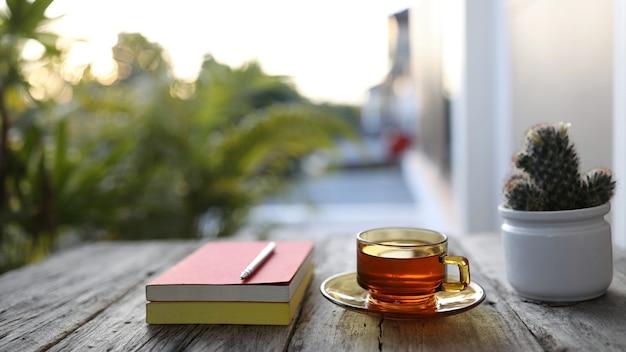 透明なガラスのお茶と屋外の木製テーブルに鉛筆でノート