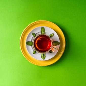 緑の壁に葉が付いているガラスのコップのお茶。時間の概念。