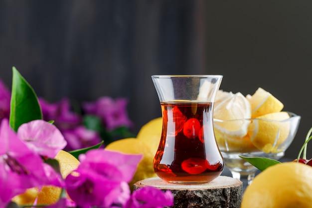 Чай в стакане с лимонами и ломтиками, цветы, деревянная доска, вид сбоку на темной поверхности