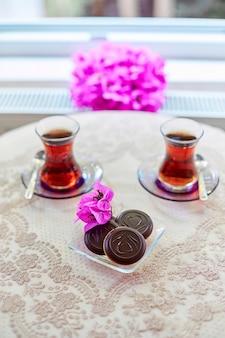 Чай в традиционных турецких стеклянных стаканах для чая на столе с печеньем.
