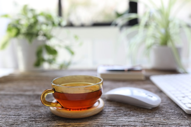 マウスとキーボードと木製のテーブルの上の透明なガラスのカップのお茶