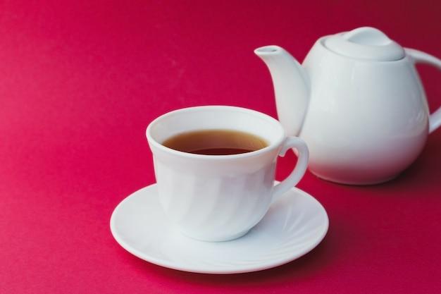 Чай в белой чашке на розовом столе.