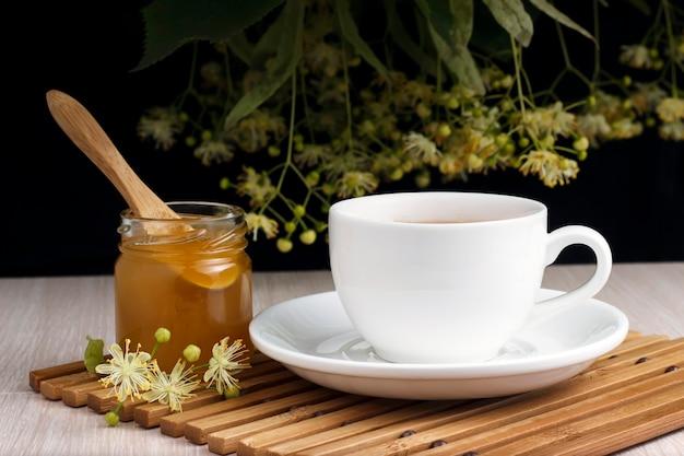 竹のスタンドにリンデン、蜂蜜の瓶とスプーンと白のお茶