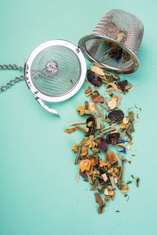 A tea infusing basket with an open tea herbs on colored backdrop