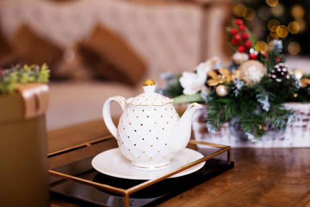 白いティーポットから白い受け皿の白いボウルにお茶を注ぐ