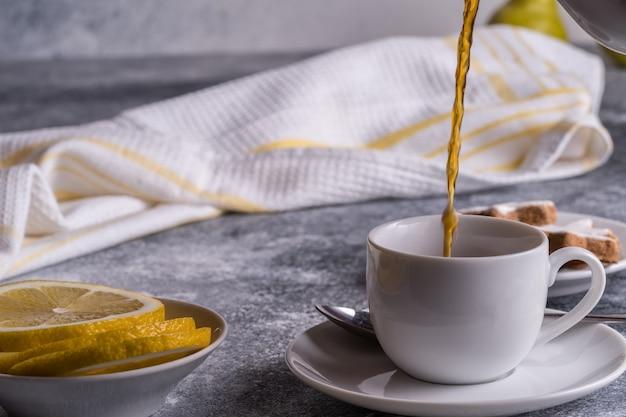 テーブルの上のカップ、クッキー、レモン、梨にお茶を注ぐ