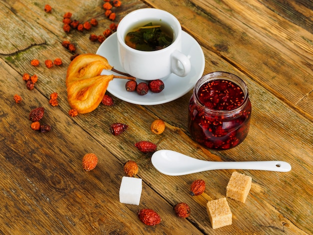 Tea, jam and dried fruit on an old wooden table.