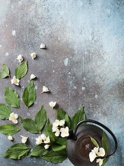 어두운 질감, 상위 뷰, 복사 공간, 수직에 주전자, 잎과 꽃 차 재스민 배경