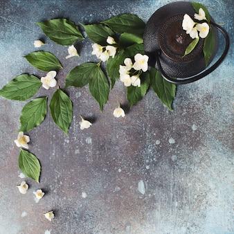 ティーポット、暗いテクスチャ、上面図、コピースペースに葉と花とお茶ジャスミンの背景