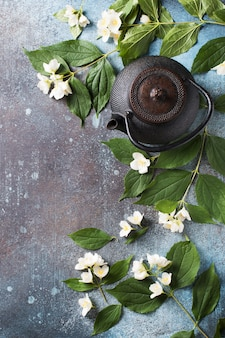 Tea jasmine background with teapot, leaves and flowers on dark texture, top view, copy space, vertical