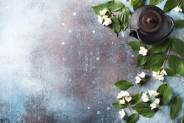 Tea jasmine background with teapot, leaves and flowers on dark texture, top view, copy space