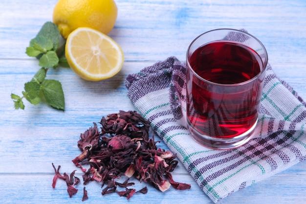 유리에 있는 차 카케이드와 푸른 나무 테이블에 히비스커스와 레몬 잎