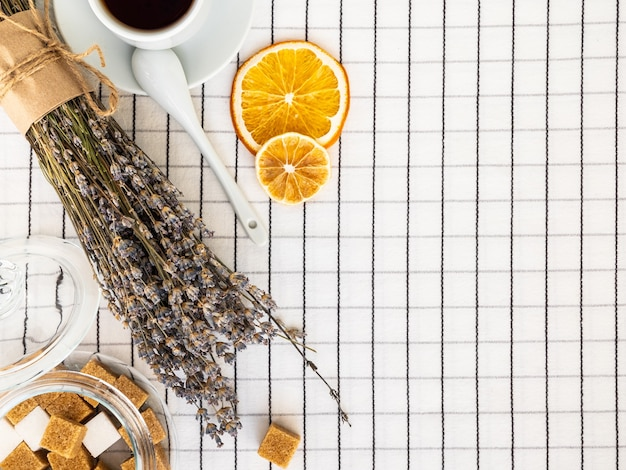Tea, lavender, sugar and lemon slices on a white checkered tablecloth.