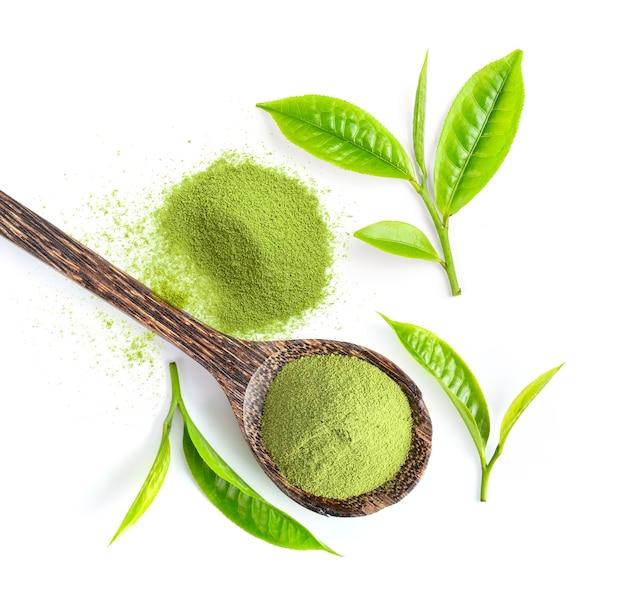 Чайный лист и порошок зеленого чая матча в деревянной ложке, изолированной на белой поверхности. вид сверху