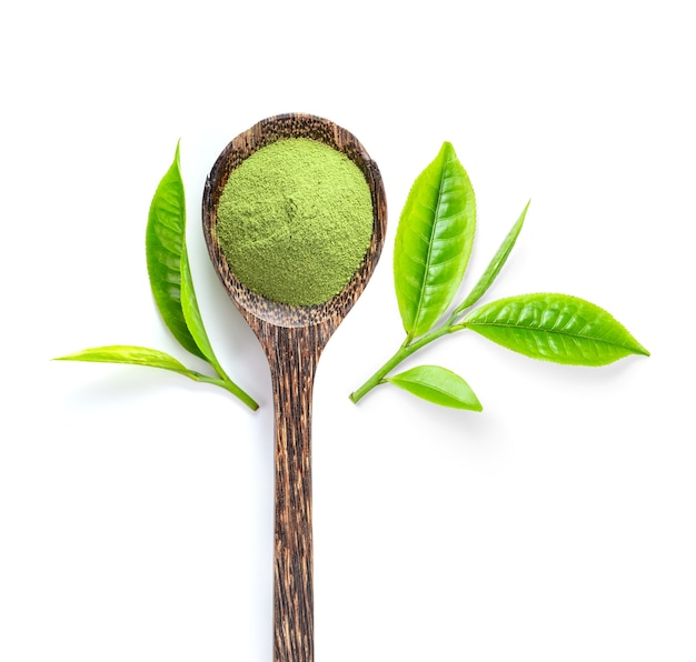 Tea leaf and matcha green tea powder in wood spoon isolated on white surface. top view