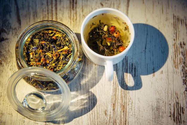 茶葉とヴィンテージの木製の背景、上面図、クローズアップのお茶。朝の光。ガラスのボウルにハーブティーとベリーを組み合わせたもの。ヘルスケア、ナチュラルドリンク、スパ、オーガニック製品のコンセプト。