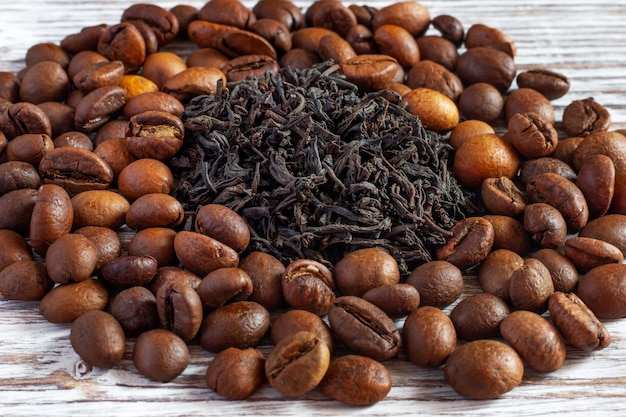 Tea leaves near coffee beans. which is better - tea or coffee